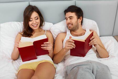 gente sentada: Feliz pareja sentada en la cama leyendo libros en el hogar Foto de archivo