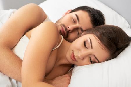 pareja durmiendo: Joven feliz pareja durmiendo en la cama