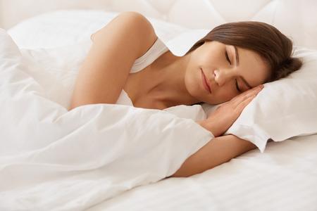 sono: Mulher nova bonita que dorme na cama Imagens