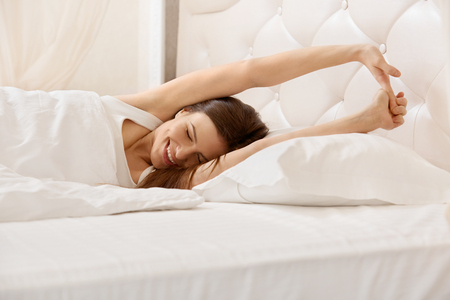 woman in bed: Woman Stretching in Her Bed.  A Girl waking up in The Morning