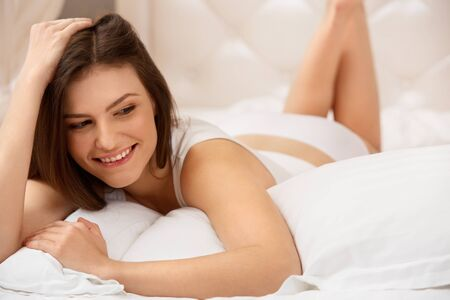 woman laying: Portrait of a pretty woman relaxing in bed