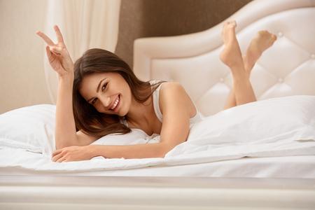 mujer en la cama: Retrato de una mujer bonita se relaja en la cama Foto de archivo