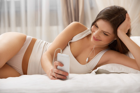 listens: Beautiful Woman Listens a Music lying on the bed