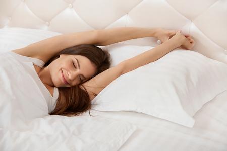 cama: Mujer que estira en su cama. Una muchacha que despierta por la ma�ana Foto de archivo