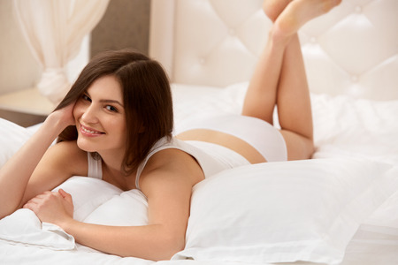 women smiling: Portrait of a pretty woman relaxing in bed