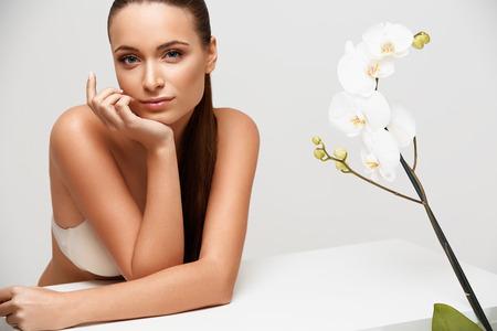 스파 여자입니다. 그녀의 얼굴을 만지고 아름 다운 소녀입니다. 완벽한 피부. 피부 관리. 웰빙 광고