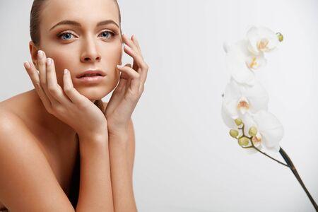 Spa Femme. Beautiful Girl toucher son visage. Perfect Skin. Soin de la peau. publicité Wellness