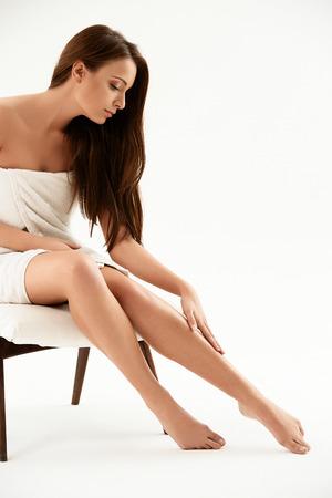 nude female body model: Long Woman Legs . Beautiful Woman Cares About Legs. Depilation Stock Photo
