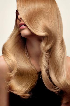 cabello: Pelo rubio. Retrato de la hermosa rubia con el pelo ondulado largo. Imagen de alta calidad.