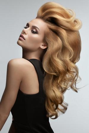 헤어 볼륨. 긴 물결 모양의 머리를 가진 아름 다운 금발의 초상화입니다. 높은 품질의 이미지입니다. 스톡 콘텐츠