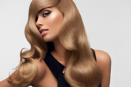 mujer sexy: Cabello. Retrato de la hermosa rubia con el pelo ondulado largo. Imagen de alta calidad. Foto de archivo