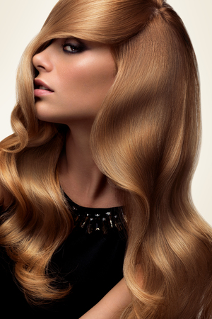 髪の毛。長いウェーブのかかった髪と美しいブロンドの肖像画。高品質の画像。