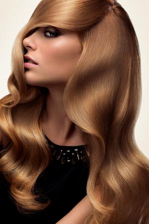 헤어. 긴 물결 모양의 머리를 가진 아름 다운 금발의 초상화입니다. 높은 품질의 이미지입니다.
