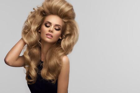 peluquerias: El volumen del cabello. Retrato de la hermosa rubia con el pelo ondulado largo. Imagen de alta calidad.