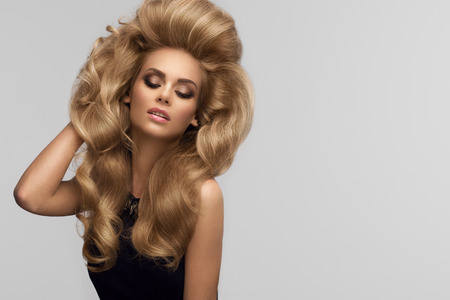 capelli biondi: Il volume dei capelli. Ritratto di bella bionda con lunghi capelli ondulati. Immagine di alta qualità. Archivio Fotografico