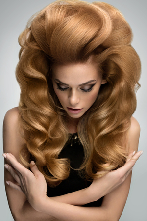 imagen: El volumen del cabello. Retrato de la hermosa rubia con el pelo ondulado largo. Imagen de alta calidad.