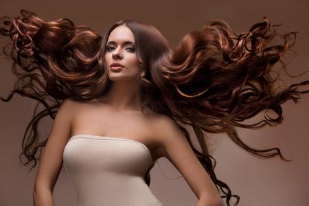 textura pelo: Cabello. Retrato de la mujer hermosa con el pelo largo del vuelo. Imagen de alta calidad. Foto de archivo