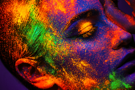 Portrait of sexy adult girl with neon makeup powder on face in studio Foto de archivo