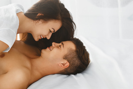 Happy smiling couple in love hugging and kissing each other while lying in bed, romantic scene in bedroom