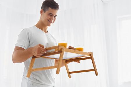 desayuno romantico: Hombre hermoso joven con desayuno rom�ntico en la bandeja