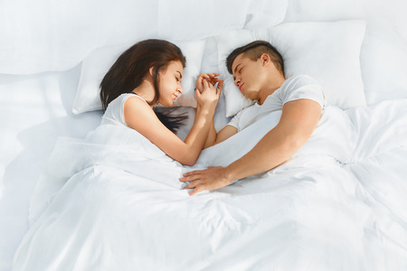 in: Portrait of young lovely couple sleeping in the bed on white blankets faced to each other