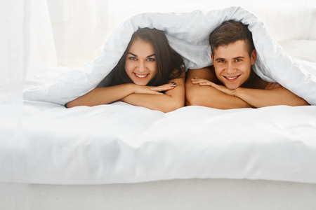 happy young couple: Young beautiful couple having fun lying on the bed under the blanket in the morning Stock Photo