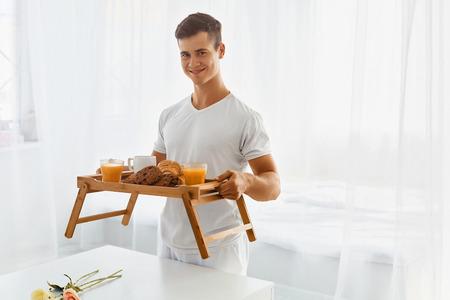desayuno romantico: Hombre hermoso joven con desayuno romántico en la cama Foto de archivo