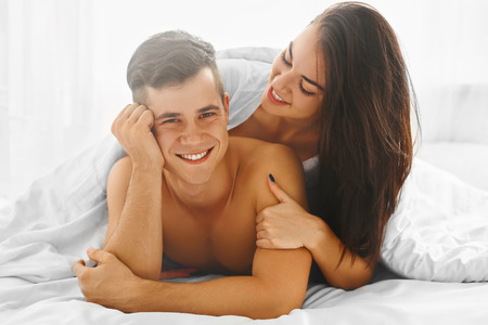 day bed: Young pretty cheerful man and woman in love lying together in the bed