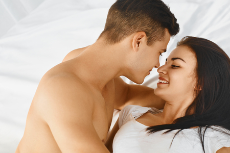 romantic kiss: Close up portrait of a young romantic couple hugging and kissing, laying down on a white bed and loving each other.