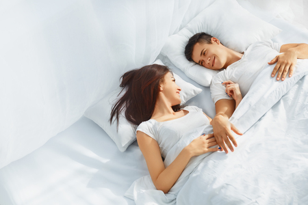 bed sheet: Young love couple lying in the bed, romantic scene in bedroom