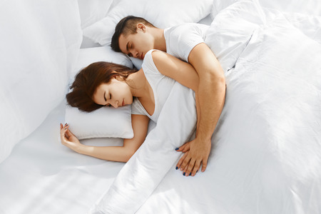 bed sheet: Young beautiful couple sleeping in the bed. Man embracing woman from behind