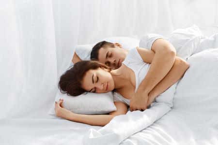 pareja durmiendo: Bella pareja joven que duerme en la cama. El hombre abrazando mujer desde atrás Foto de archivo