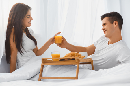 breakfast in bed: Young happy couple in love eating breakfast and enjoying each other in bed in the morning Stock Photo