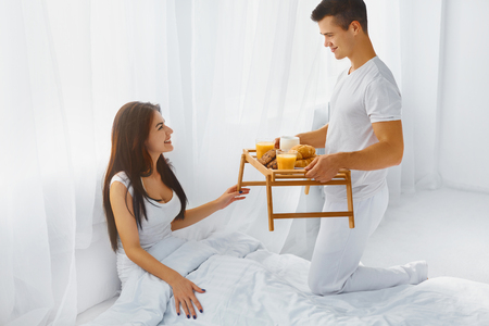 breakfast in bed: Handsome smiling man surprising his attractive happy woman with romantic breakfast in bed in the morning Stock Photo