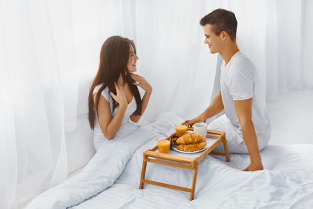 romantic man: Handsome smiling man surprising his attractive happy woman with romantic breakfast in bed in the morning Stock Photo