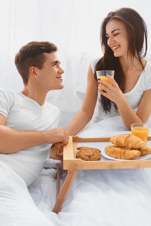 desayuno romantico: Pareja joven y atractiva que tiene un rom�ntico desayuno en la cama por la ma�ana