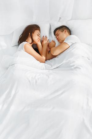 Retrato de jovem casal lindo dormir na cama em cobertores brancos enfrentaram uns aos outros