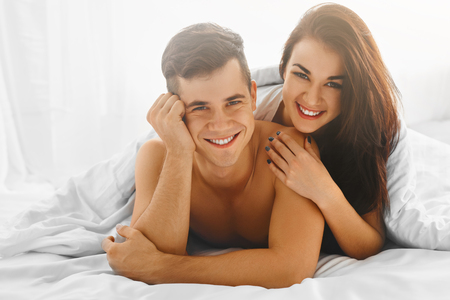 day bed: Young pretty cheerful couple in love lying together in the bed