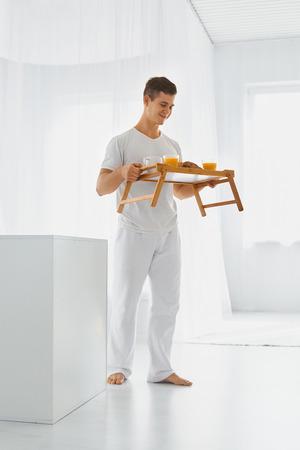 desayuno romantico: Hombre hermoso joven con desayuno romántico en la bandeja. Amor y cuidado. Fondo blanco.