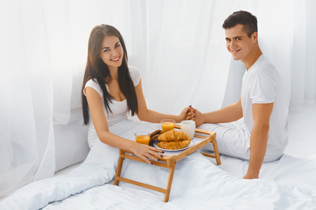 young wife: Young handsome husband serving his beautiful happy wife breakfast in bed . Love and care. Relationships concepts.