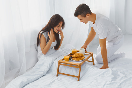 desayuno romantico: Hombre sonriente hermoso sorprendiendo a su atractiva mujer feliz con desayuno romántico en la cama por la mañana Foto de archivo