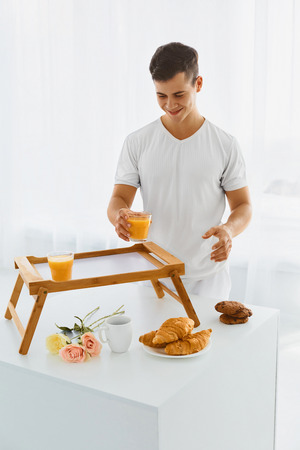 pyjama: Young handsome man putting two glasses of orange juice, croissant, cookies and coffee on the bed tray decorating it with pastel roses Stock Photo
