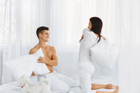 couple fight: Portrait of happy beautiful couple in love having a pillow fight in bed in the morning Stock Photo