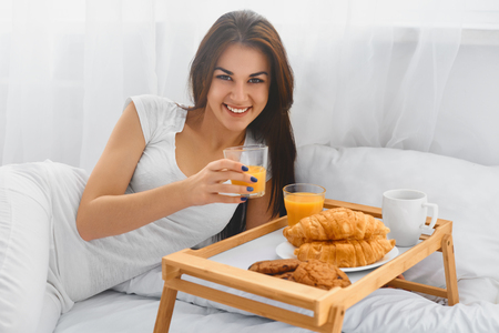 lifestyle caucasian: Attractive girl eating breakfast in bed and smiling at camera in the morning