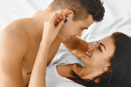 romantic man: Close up portrait of a young romantic couple hugging and kissing, laying down on a white bed and loving each other Stock Photo