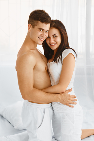 sexual intimacy: Handsome man and beautiful woman embracing in bedroom Stock Photo