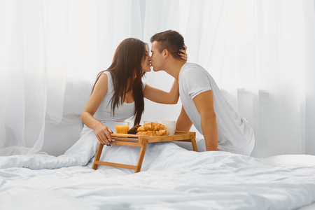 petit dejeuner romantique: Young attractive man serving pretty smiling woman romantic breakfast in bed in the morning