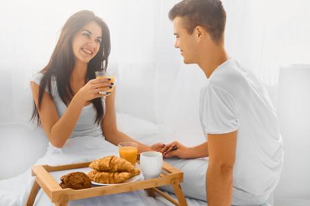 desayuno romantico: Sonriente pareja de jóvenes felices tienen romántico desayuno en la cama por la mañana Foto de archivo