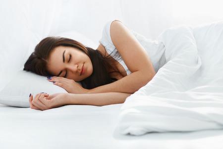 幸せな美しい白人の女の子は朝自宅寝室で快適なベッドの枕で寝ています。