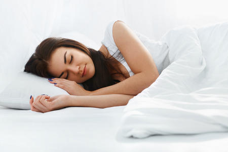 girl lying: Happy beautiful caucasian girl sleeping on the pillow in comfortable bed in the bedroom at home in the morning